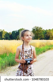 Cute little girl taking pictures with old film camera.  Pretty child in nature. Place for text
