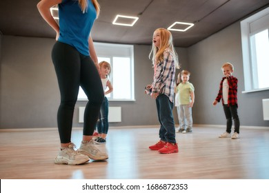 Cute little girl is talking with her female dance teacher while standing in the dance studio. Group of cute little boys and girls studying modern dance in choreography class. Sport. Active lifestyle