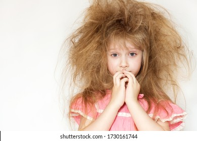 a cute little girl with tangled long hair in a pink dress on a white background.