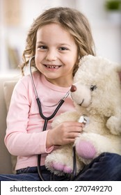 Cute little girl with  teddy bear and stethoscope.