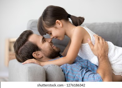 Cute little girl tenderly touching noses with happy dad lying on sofa, kid daughter and father having fun bonding feeling love connection enjoy relaxing together, daddy and child warm relationships