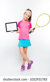 Cute little girl with tennis racket and tablet in her hands on white background