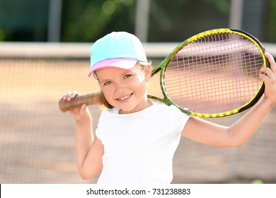 Cute little girl with tennis racket on court