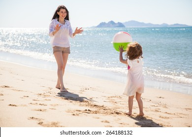 Cute little girl throwing a beach ball at her mom and having some fun on a sunny day