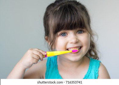Cute little girl with a toothbrush in her hand cleans her teeth and smiles.