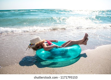 Cute little girl with toy floating ring on the beach. Family, summer vacation concept.