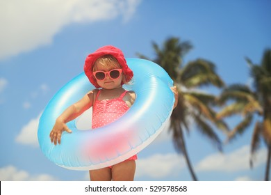 cute little girl with toy floating ring at tropical beach