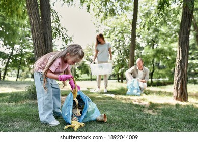 Cute little girl with trash bag collecting garbage while cleaning with parents in the park or forest. Environmental conservation and ecology, recycling and concept