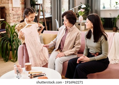 Cute little girl trying on new dress bought in online shop by her mother and grandmother while standing in front of them in living-room