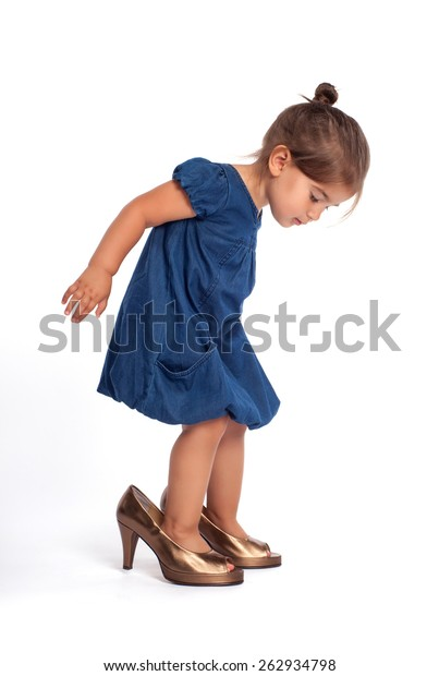 Cute little girl trying to walk with big high heel shoes