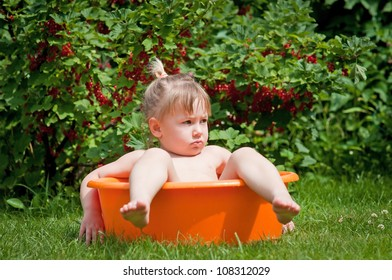Cute little girl in a tub in a summer garden with berries in the background