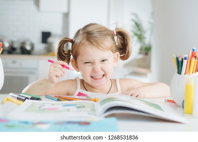 Cute little girl with two tails is drawing in coloring book with colored pencil at home. Angry grin. Blurred background.