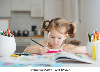 Cute little girl with two tails is drawing in coloring book with colored pencil at home. Blurred background.