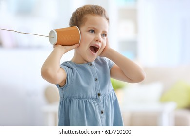 Cute little girl using plastic cup as telephone while playing at home