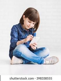 Cute little girl using smart phone