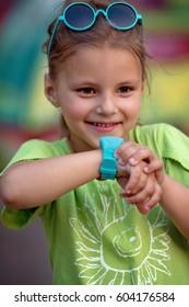 Cute little girl is using smartwatch.