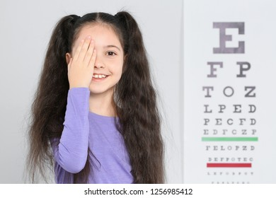 Cute little girl visiting children's doctor, space for text. Eye examination