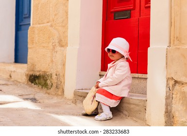 cute little girl waiting at the door on the street of Malta, Europe