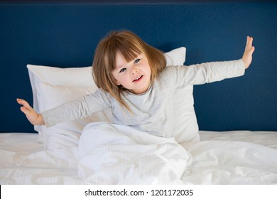 Cute little girl wake up and stretch on bed in morning. lazy concept