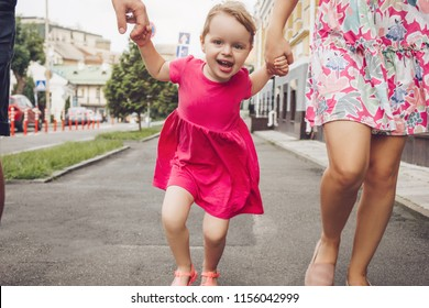 cute little girl walk the street with parents