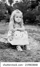 cute little girl for a walk upset sitting on a tree stump (black and white)