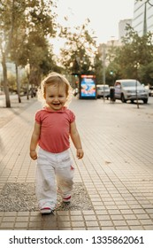 Cute little girl walking on the street happy at sunset