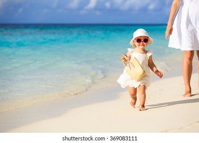cute little girl walking on the beach with mother