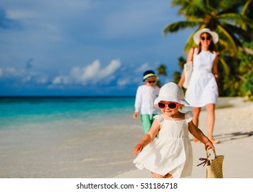 cute little girl walking on beach with family