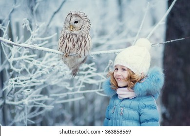Cute little girl in warm clothes blue and white, looking at an eagle Owl sitting on a branch covered with frost on a cold winter day. Children and nature.