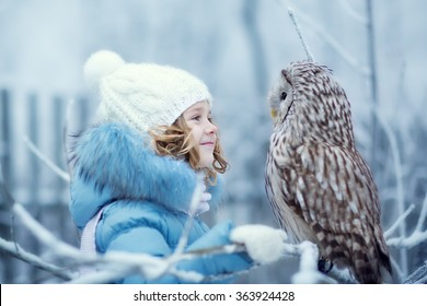 Cute little girl in warm clothing looking at an eagle Owl sitting on a branch covered with frost on a cold winter day. Children and nature.