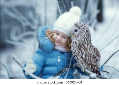 Cute little girl in warm clothing, looks and hugs Owl sitting on a branch covered with frost on a cold winter day. Children and nature. Children and nature.