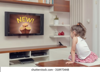 cute little girl watching advertisement on tv. Appropriate content for kids. Coppa concept.