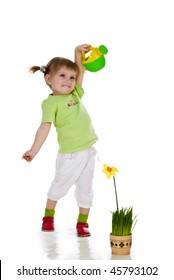 Cute little girl watering the flower. Studio shot