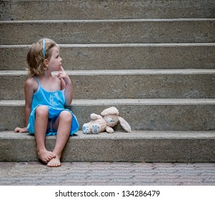 cute little girl wearing blue dress sitting on concrete steps with her stuffed bunny