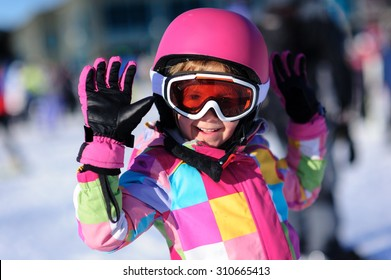 Cute little girl wearing a bright colorful winter jacket and a pink ski helmet and goggles waiving at the camera
