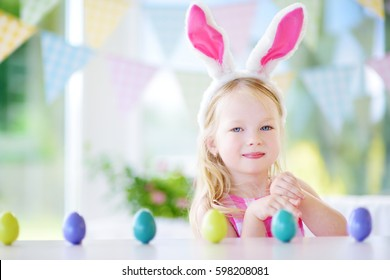 Cute little girl wearing bunny ears playing egg hunt on Easter. Adorable child celebrate Easter at home.