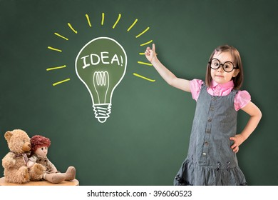 Cute little girl wearing business dress and showing a light bulb on green chalk board.