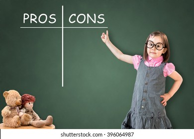 Cute little girl wearing business dress and showing pros and cons comparison concept on green chalk board.