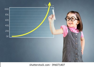 Cute little girl wearing business dress and drawing over target achievement graph. Blue background.