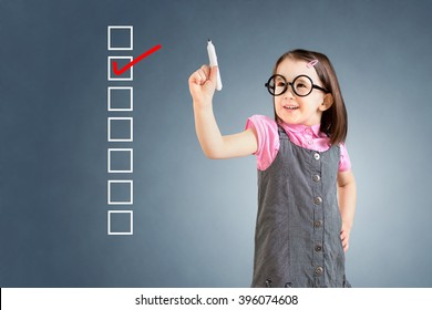 Cute little girl wearing business dress and checking on checklist box. Blue background.