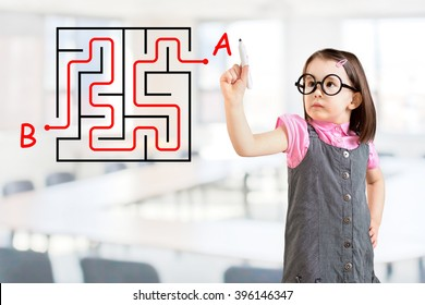 Cute little girl wearing business dress and finding the maze solution writing on the whiteboard. Office background.