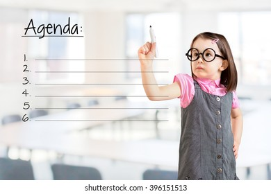 Cute little girl wearing business dress and writing blank agenda list. Office background.