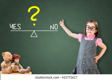 Cute little girl wearing business dress and showing yes and no compare on balance bar on green chalk board.