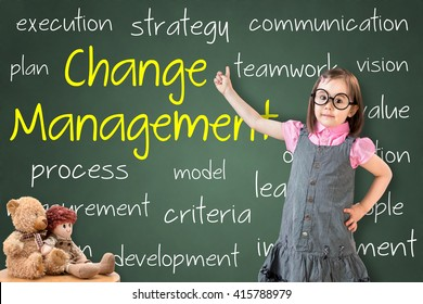 Cute little girl wearing business dress and showing change management concept on green chalk board.