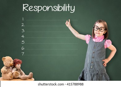 Cute little girl wearing business dress and showing responsibility list in blank on green chalk board.