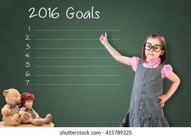 Cute little girl wearing business dress and showing blank 2016 goals list on green chalk board.