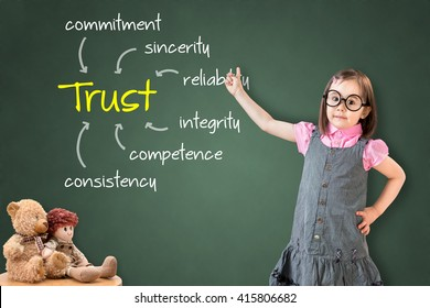 Cute little girl wearing business dress and showing trust building concept on green chalk board.