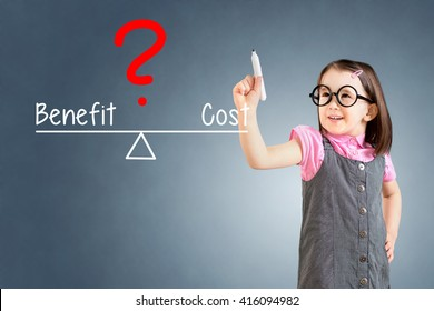 Cute little girl wearing business dress and writing cost and benefit compare on balance bar. Blue background.
