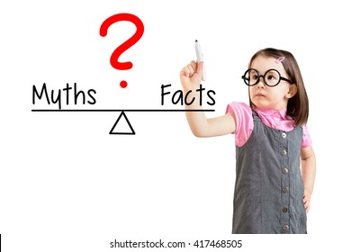 Cute little girl wearing business dress and writing myths and facts compare on balance bar. White background.
