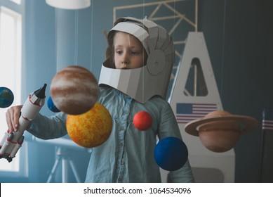 Cute little girl wearing cardboard astronaut helmet flying toy rocket through planets, cardboard spaceship rocket in the background